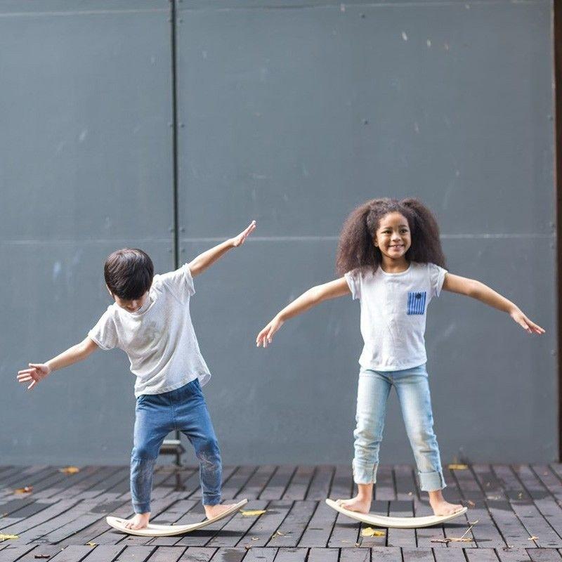 Niños haciendo equilibrio con tabla curva
